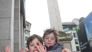 two boys review the monument to the great fire of london